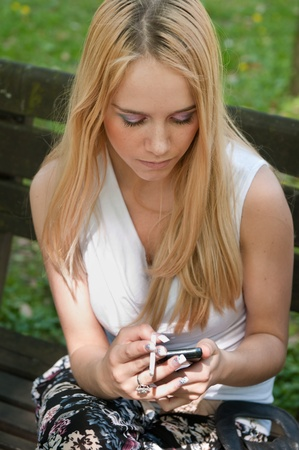 women smoking: Unhappy teenager with mobile phone