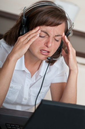 Young business person with headache working with computer(headset on head) Stock Photo - 10711428