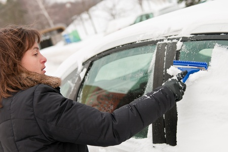 Young woman cleaning car windows from snow in winter season photo