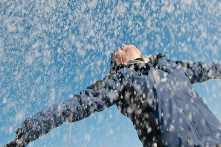 Young woman throwing snow on blue sky in background - joy and happines emotions Stock Photo - 10711502