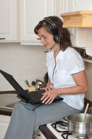 personas comunicandose: Empresario joven con trabajo de auriculares de casa portátil mientras se hace la comida en la cocina