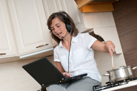 home office interior: Young business woman having work conference call from home while cooking meal in kitchen Stock Photo