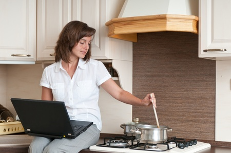 Young woman cooking meal in kitchen according to receipt from laptop (internet) photo
