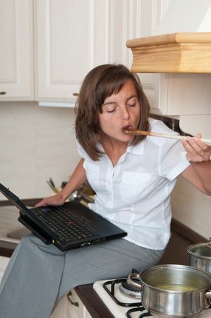 Multitasking woman - cooking meal and working photo