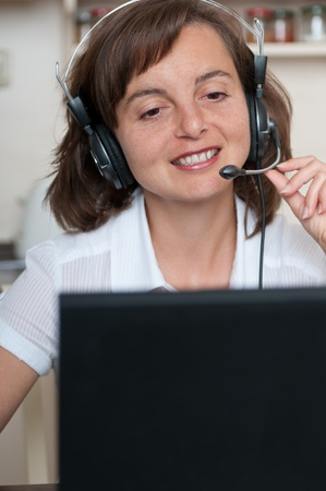 Young business person with headache working at home and calling (headset on head) Stock Photo - 10711473