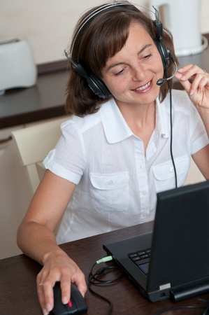 Young business person with headache working at home and calling (headset on head) Stock Photo - 10711474