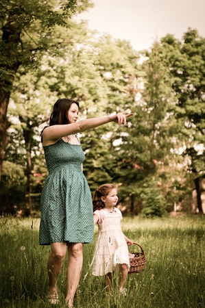 Mother shows with finger to her cute little daughter something interesting in distance photo