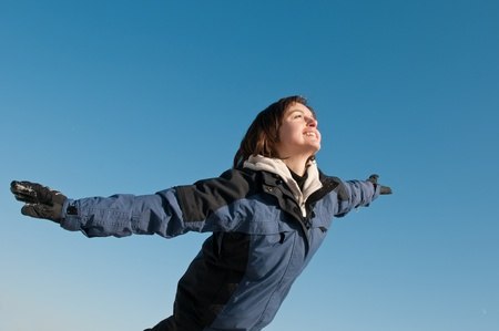 having fun in winter time: Young woman having fun on blue sky in winter time - joy and happines emotions