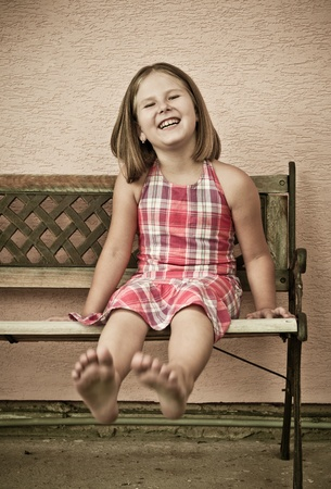 young girl barefoot: Portrait of cute child sitting on bench and stretching barefoot legs - sepia toning Stock Photo