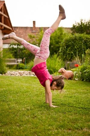 Child doing handstand in backyard photo