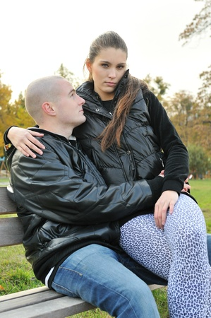 man woman hugging: Young couple in love outdoors - sitting on knees Stock Photo