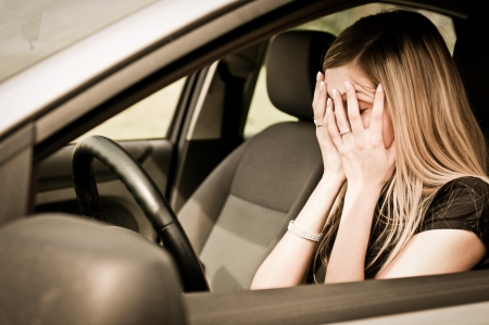 accident car: Young woman with hands on eyes sitting depressed in car