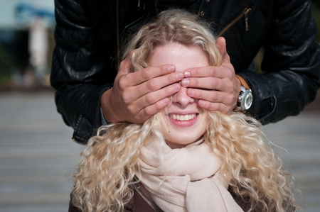 Hands of man covering eyes of young smiling blond woman - outdoor photo