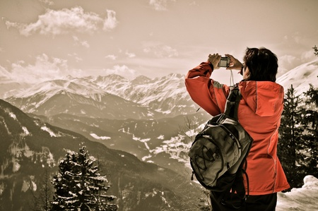photographing: Senior woman with backpack holding camera and taking picture in winter mountains - rear view