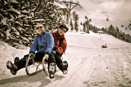 pensioners: Active senior couple on sledge having fun in mountain snowy country