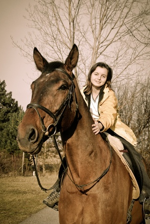 Young woman riding on big brown horse with in sunny day photo