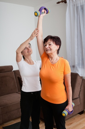 senior fitness: Coach assisting senior woman exercising with barbells