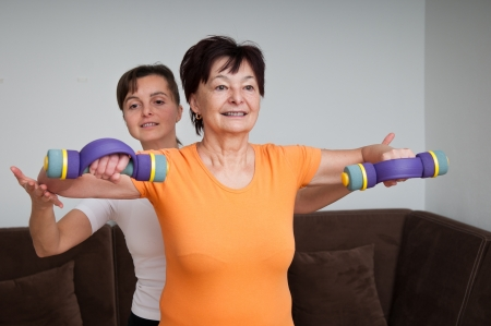 home trainer: Senior woman exercising with trainer
