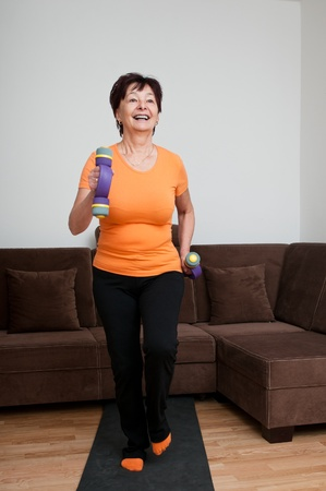 Smiling mature fitness woman excercising with barbells at home - walking photo