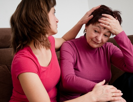 senior depression: Daughter (young woman) comforts her depressed senior mother at home