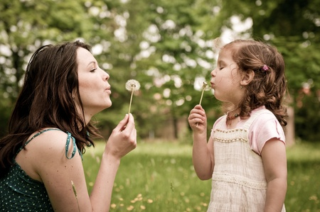 love blow: Mother with small daughter blowing to dandelion - lifestyle outdoors scene in park