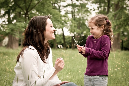 happy family nature: Mother with small daughter blowing to dandelion - lifestyle outdoors scene in park