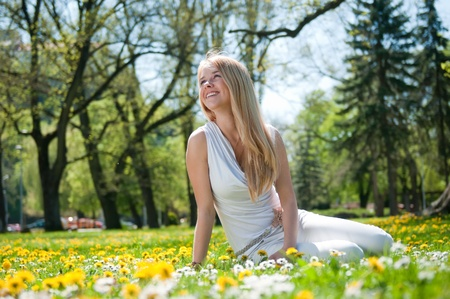 Smiling happy young person (teenager) sitting outdoors in blooming grassfiled and looking away photo