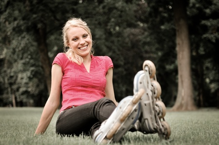 Young smiling woman relaxing in green grass after roller blading photo