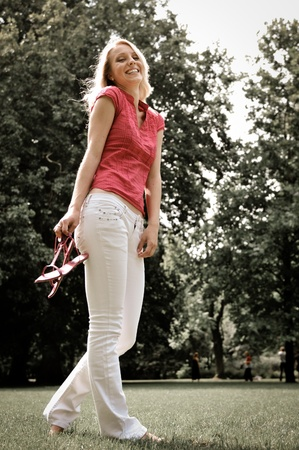 Smiling young woman holding her shoes and walking barefoot on grass in park photo