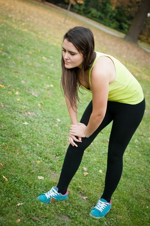 cramp: Knee injury - woman in pain after sport
