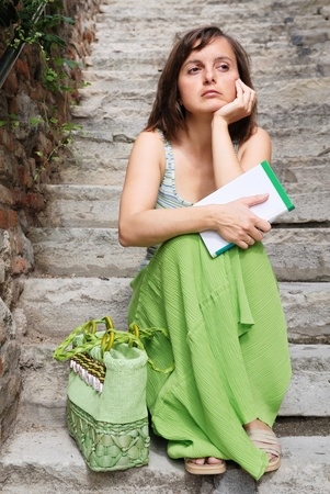 Young woman dressed in green with thoughtful look sits on stairs and holds book  Stock Photo