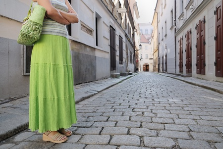 Young woman in green skirt standing on paving road (with street in backlground) photo
