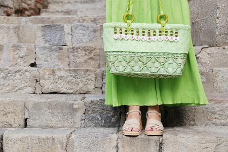 Detail (torso) of young woman in green skirt waiting on stairs photo