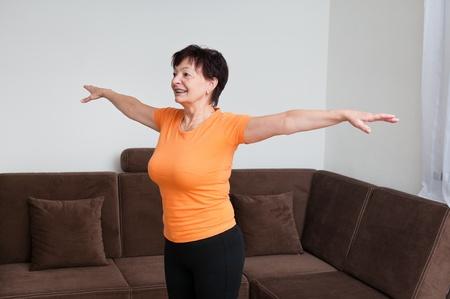 Senior fitness woman exercising at home photo