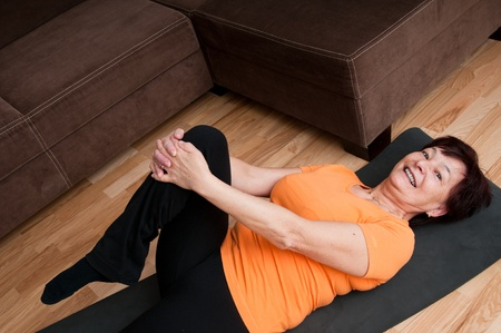 senior home: Mature fitness woman exercising at home Stock Photo