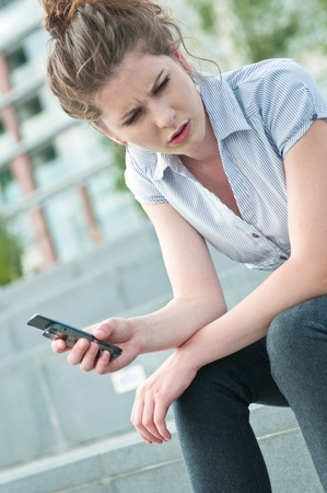 Young worried woman with unhappy expression holding mobile phone - outdoors in urban setting photo