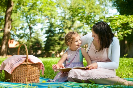 Mother and child reading book on picnic in park Stock Photo
