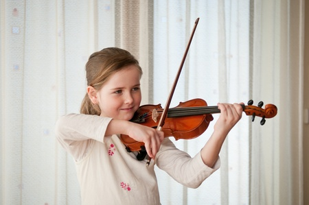 Child playing violin indoors photo