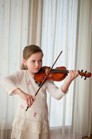 Child playing violin at home photo
