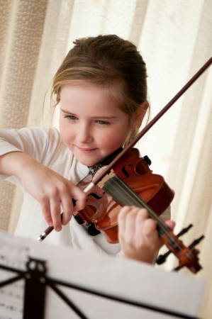 stringed instrument: Child playing violin at home