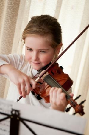 instruments de musique: Violon enfant jouant � la maison Banque d'images