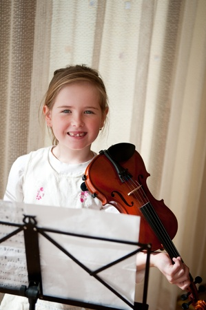 Child holding violin at home photo