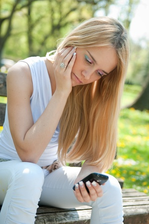 Unhappy teenager with mobile phone Stock Photo - 12588422