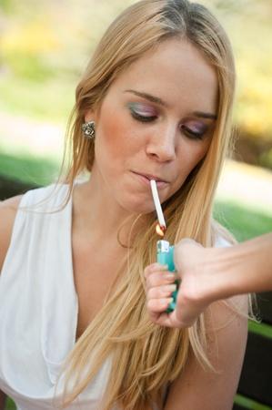 Smoking teenager - lighting cigarette photo