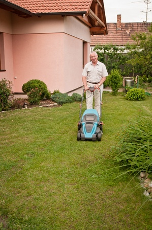 mowing grass: Senior man with lawn mower Stock Photo