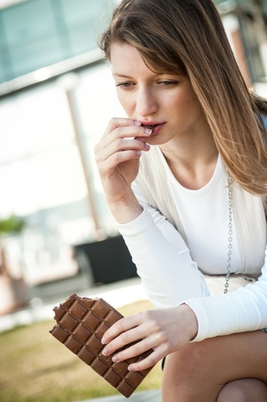 Depressed young woman eating chocolate photo