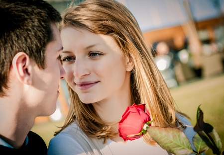 dating and romance: Young couple - woman with red rose