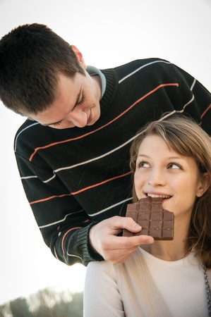 tenager: Young couple in locve eating chocolate