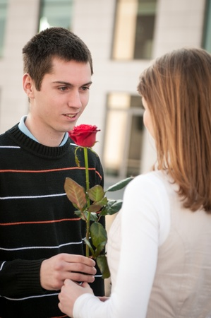 Young man handing over a flower to woman photo