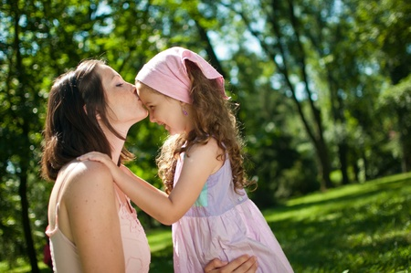 hand on forehead: Love - mother kissing her child Stock Photo